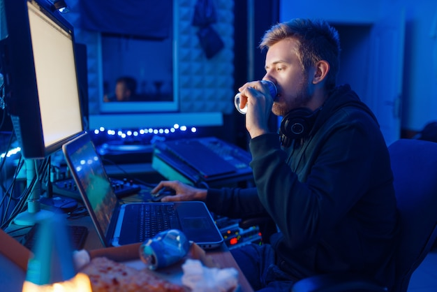 Male gamer drinking an energy drink at his workplace with laptop and desktop pc, gaming night lifestyle. computer games player in his room with neon light, streamer Premium Photo