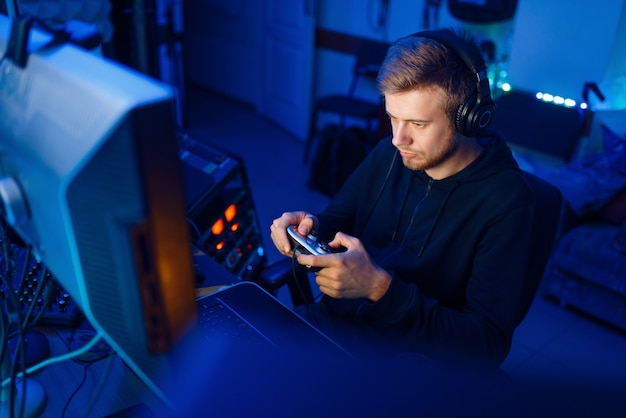 Male gamer in headphones holds joystick and playing videogame on console or desktop pc, gaming lifestyle, cybersport. computer games player in his room with neon light, streamer Premium Photo