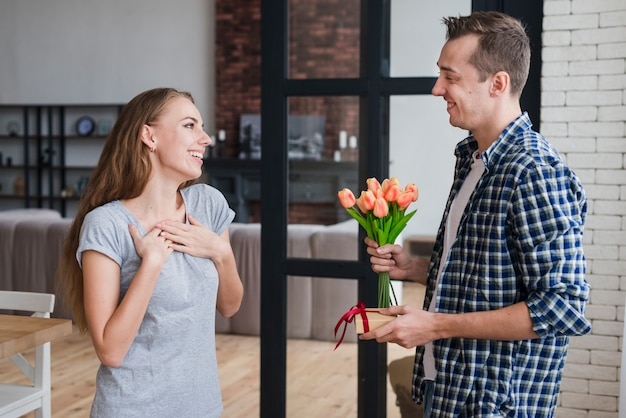Male giving flowers and gift to wife Free Photo