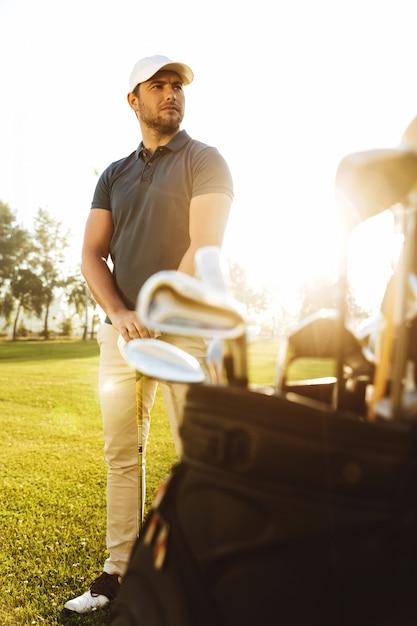 Мужской игрок в гольф на зеленом поле с клубным мешком Бесплатные Фотографии