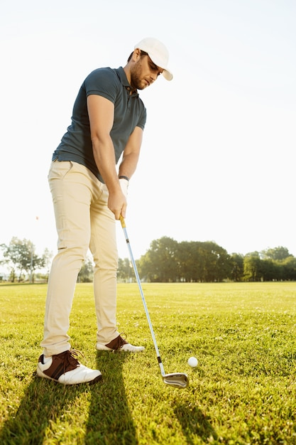 Male golfer about to tee off a golf ball Free Photo