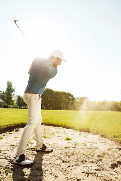 Male golfer hitting ball out of a sand trap Free Photo