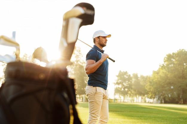 Мужчина гольфист держит водителя стоя Бесплатные Фотографии