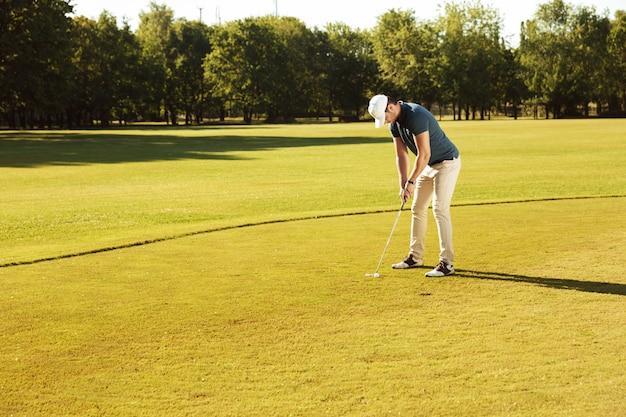 그린에 골프 공을 퍼 팅하는 남성 골퍼 무료 사진