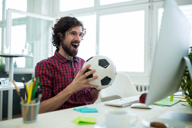 Male graphic designer cheering while watching football match Free Photo