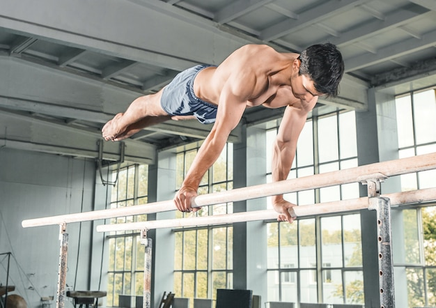 Male gymnast performing handstand on parallel bars Free Photo