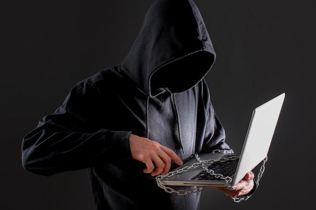Мужской хакер с ноутбуком защищен цепью Бесплатные Фотографии