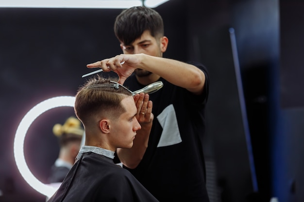 Male haircut with electric razor. barber makes haircut for client at the barber shop by using hairclipper. man hairdressing with electric shaver. Premium Photo
