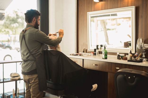 Male hairdresser combing hair of senior client Free Photo