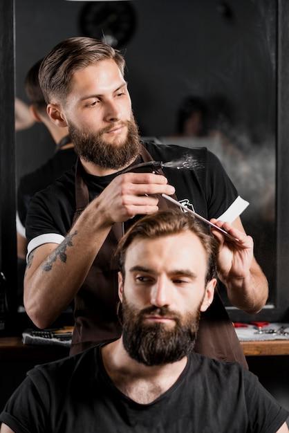 理髪店で男性の美容師の髪を切る Premium写真