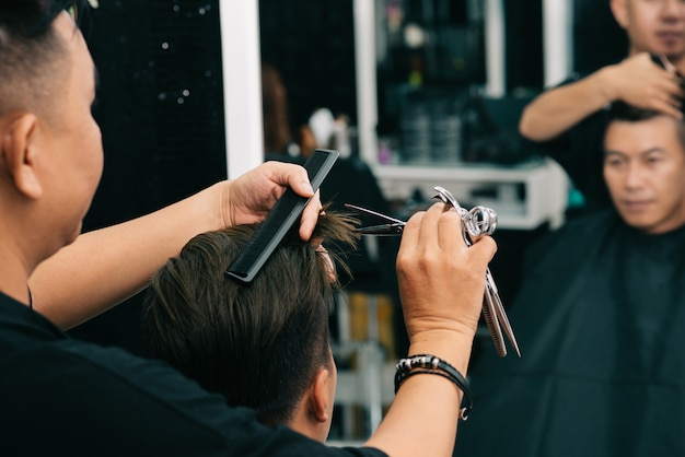Male hairdresser cutting customer's hair with comp and scissors in front of mirror Free Photo