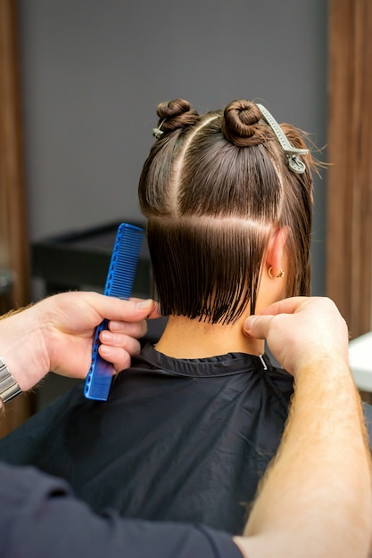 Male hairdresser cutting hair of young woman holding comb at hair salon. Premium Photo