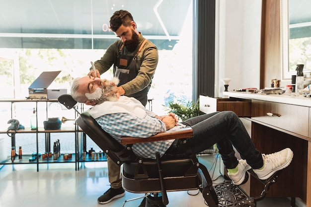 Male hairdresser preparing for shaving senior client in barbershop Free Photo