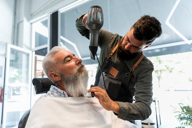 Male hairdresser using dryer for beard of senior client Free Photo