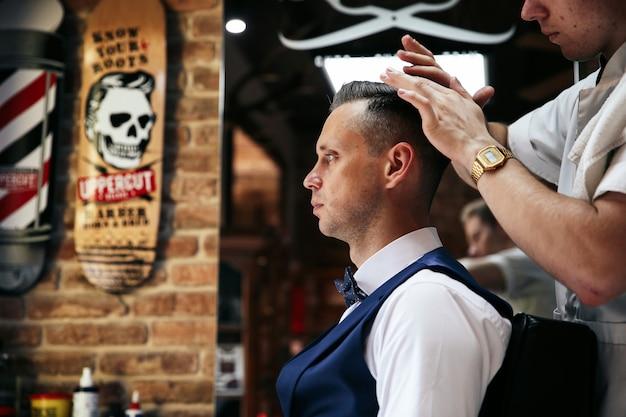 Il parrucchiere maschio sta servendo il cliente facendo parrucchiere Foto Gratuite