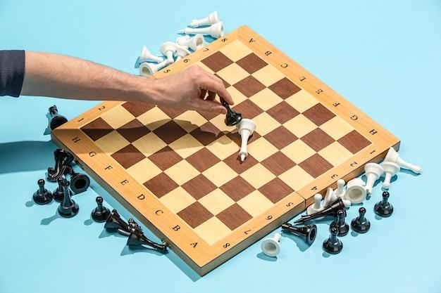 男性の手とチェス盤、ゲームのコンセプト。 無料写真