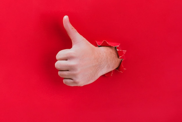Male hand breaks through the red paper and shows his thumb up. Premium Photo