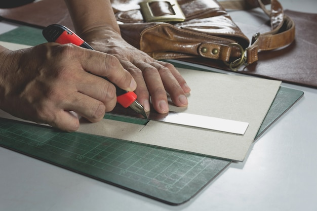 Male hand cutting with a knife to pattern for bag. home made product concept. Premium Photo