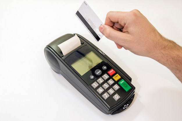 Male hand dials pin code on pin pad of card machine or pos terminal with inserted blank white credit card isolated on white background. payment with credit card - businessman holding pos terminal. Free Photo