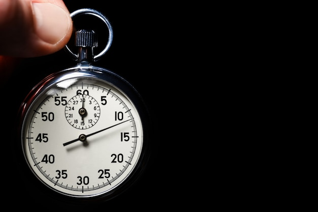 Male hand hold the analog stopwatch on a black background, close-up, isolate, copy space Premium Photo