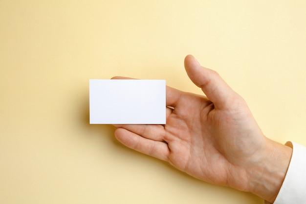 Мужская рука держит пустую визитную карточку на мягкой желтой стене для текста или дизайна. пустые шаблоны кредитных карт для связи или использования в бизнесе. финансы, офис. copyspace. Бесплатные Фотографии