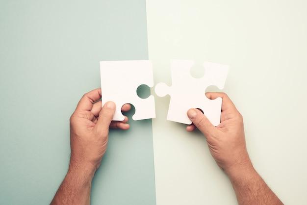 大きな紙の白い空白のパズルのピースを持っている男性の手 Premium写真
