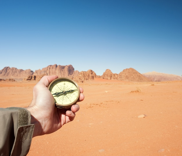 Male hand holding compass in the desert Premium Photo