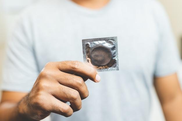 Male hand holding condom. safe sex concept. Premium Photo