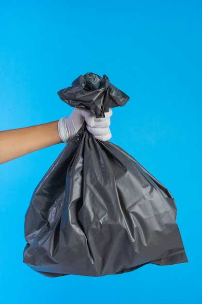 The male hand holding a garbage bag and a blue . Free Photo