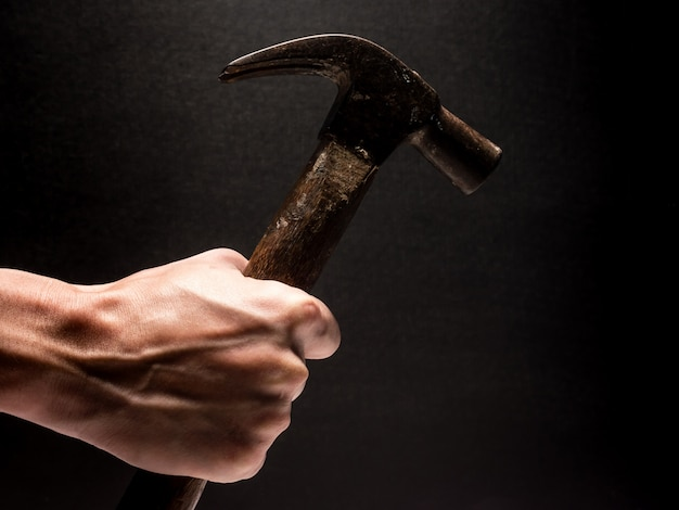 Male hand holding hammer on black background Premium Photo