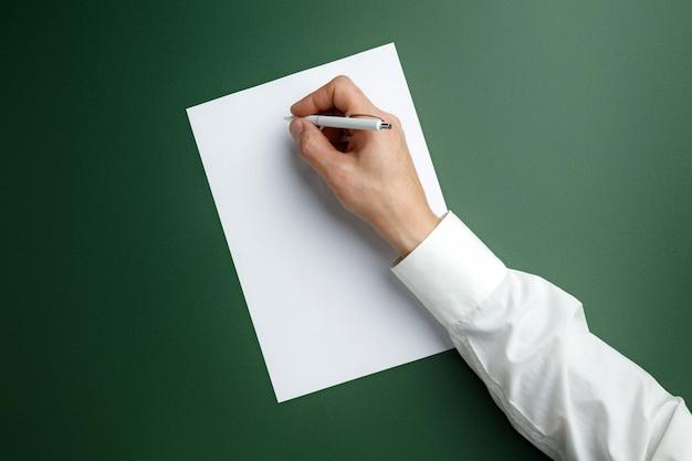 Мужская рука держит ручку и писать на пустой лист на зеленой стене для текста или дизайна. пустые шаблоны для контактов, рекламы или использования в бизнесе. финансы, офис, покупки. copyspace. Бесплатные Фотографии