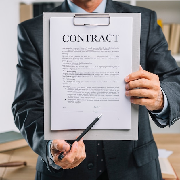 Male hand holding pen pointing at signature place on a contract document Free Photo