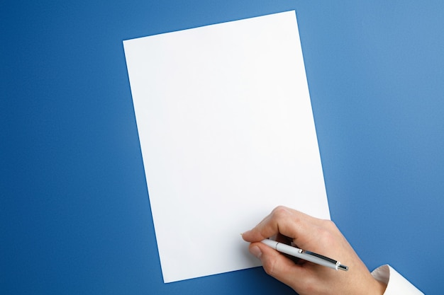 Male hand holding pen and writing on empty sheet on blue wall for text or design. blank templates for contact, advertising or use in business. finance, office, purchases.  copyspace. Free Photo