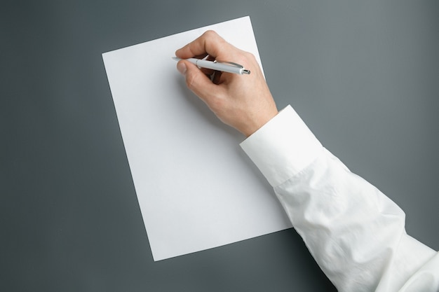 Male hand holding pen and writing on empty sheet on grey wall for text or design. blank templates for contact, advertising or use in business. finance, office, purchases.  copyspace. Free Photo