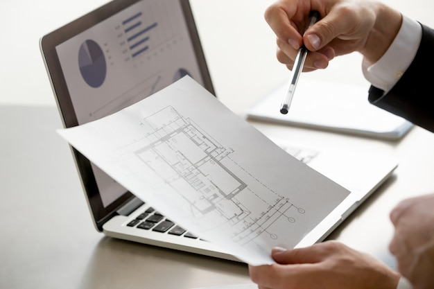Male hand holding project plan, statistics on screen, close up Free Photo