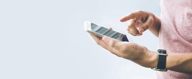 スマートフォン、バナーサイズの背景にコピースペースを持つ携帯電話を持っている男性の手。 Premium写真