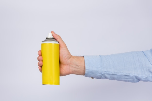Male hand holding yellow spray bottle on white wall. copy space, mock up. side view Premium Photo