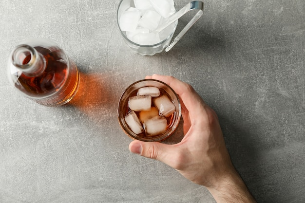 Male hand holds glass of whiskey on grey background with bottle and ice cubes, top view Premium Photo