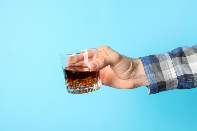 Male hand holds glass of whiskey with ice cubes on blue background, space for text Premium Photo