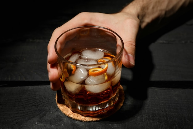 Male hand holds glass of whiskey with ice cubes on wooden background, close up Premium Photo