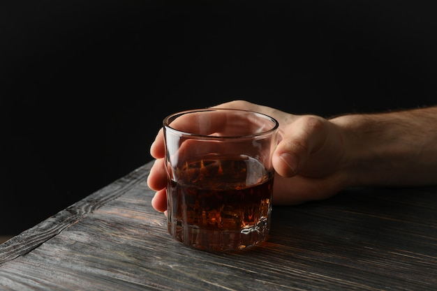 Male hand holds glass of whiskey with ice cubes on wooden background, space for text Premium Photo