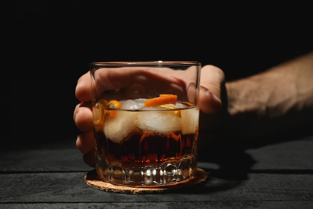 Male hand holds glass of whiskey with orange peel on wooden background, space for text Premium Photo