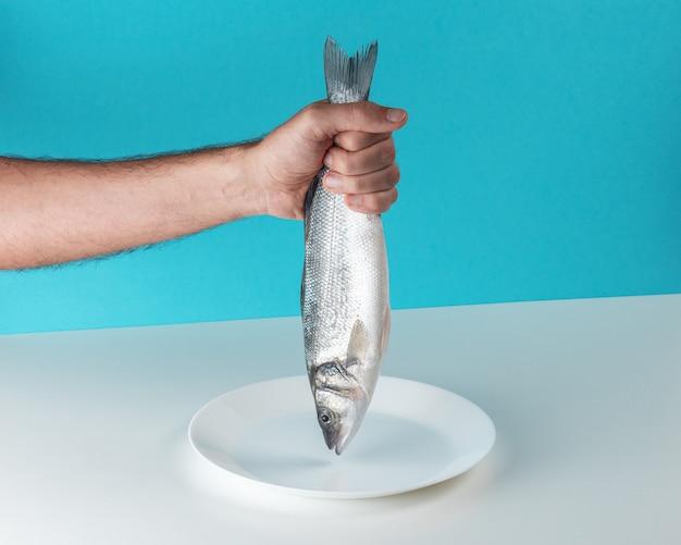 Мужская рука держит сырую свежую рыбу морского окуня Premium Фотографии