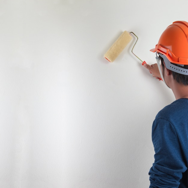 Мужской ручная роспись стены с валиком, ремонт белой краской. Premium Фотографии