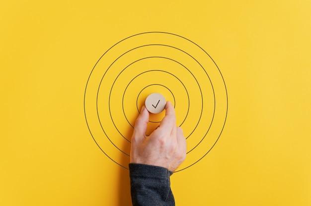 黄色の背景の上に描かれた円の真ん中にチェックマークが付いた木製のカット円を置く男性の手。 Premium写真