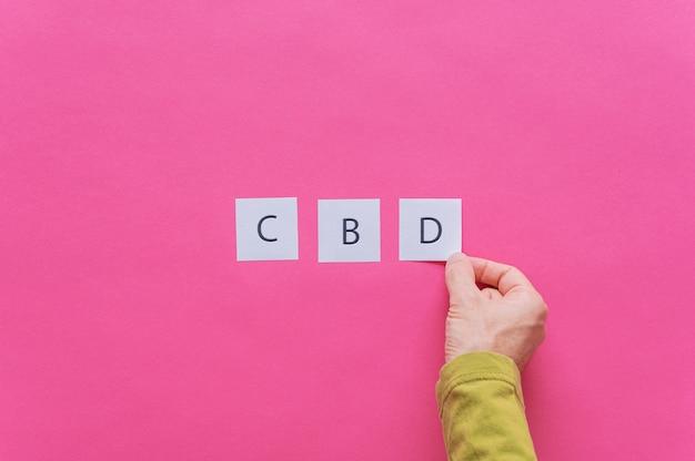흰색을 배치하는 남성 손은 Cbd를 철자하기 위해 연속으로 글자가있는 서류를 게시합니다. 프리미엄 사진