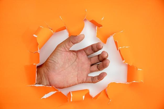 Male hand ripped orange paper Premium Photo