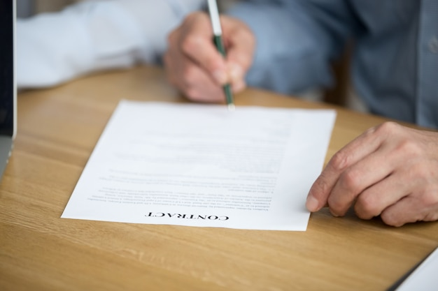 Male hand signing contract, senior man putting signature on document Free Photo