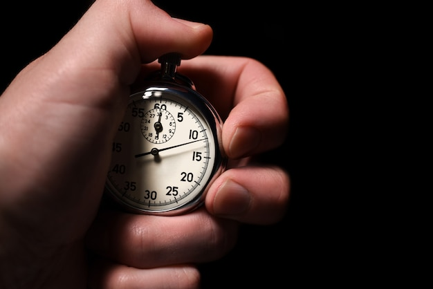 Male hand starts the analog stopwatch on a black background, close-up, isolate, copy space Premium Photo