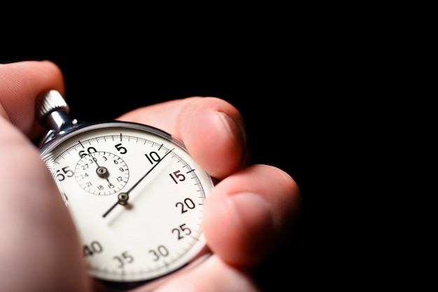 Male hand starts the analog stopwatch on a black background Premium Photo